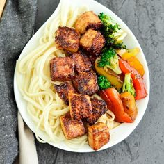 overhead view of crispy tofu with hoisin sauce on a plate with noodles and stir fried veggies