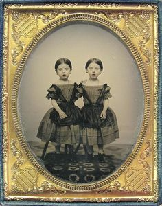 Ambrotype - The Watts Twins in Summer Dresses  This 1/2 plate ambrotypes shows twin girls standing on a carpeted platform. They wear identical off the shoulder dresses. In the background are sets of legs that appear to be braces to hold them still although they are not the standard upright on a heavy base.  A second ambrotype shows them in identical fur trimmed coats and hats.  source: http://www.flickr.com/photos/20939975@N04/2169400604/in/photostream
