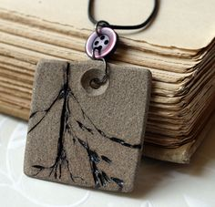 Stoneware Pendant - Unglazed except native grass imprint.  Like the button link and the indentation for the jumpring