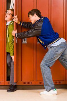 High school jock pushing nerd in locker
