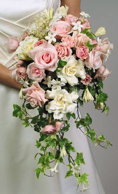 Cascade bouquet of white gardenias, roses, pink spray roses, stephanotis ivy, galax leaves and Italian rucus. Found on La Rosa's Flowers #cascadebouquet