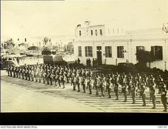 Tobruk, North Africa. 1941-02. Members of the Guard of Honour of 2/1st Infantry Battalion, present arms on the arrival of Mr Robert Menzies, Leader of the Opposition in the Australian House of ...