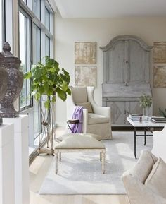 crusty canvases, pale blue-grey cabinet, sleek ottoman and wing chair...