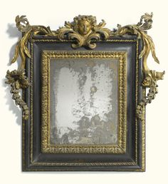 An Italian carved giltwood and ebonised mirror, Roman, late 17th/early 18th century