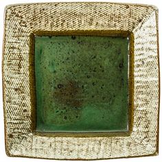 Tatsuzo Shimaoka Large square stoneware plate, press moulded the rim with rope and slip inlaid pattern, the centre covered in a green glaze, with signed wood box. W. 295mm