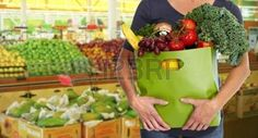 hands shopping vegetables: Woman with grocery bag of vegetables over store background.