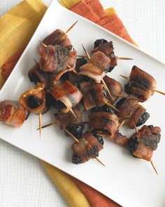 8 slices bacon, 24 prunes Preheat oven to 400 degrees. Line a large rimmed baking sheet with foil. Wrap bacon pieces around prunes and secure with toothpicks. Bake on sheet until bacon is browned, about 15 minutes, flipping halfway through. Halloween Party Appetizers, Thanksgiving Appetizers, Holiday Appetizers, Birthday Appetizers, Halloween Entertaining, Quick And Easy Appetizers, Easy Appetizer Recipes, Easy Recipes, Appetizer Dishes