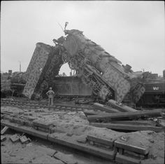 BRITISH ARMY NORTH-WEST EUROPE 1944-45 (BU 2942)   A British soldier is dwarfed by a German railway locomotive resting at a precipitous angle in a heavily-bombed railyard in Munster, 3 April 1945.