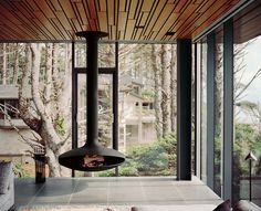 A wood-burning stove by Euroflues is suspended from the ceiling in the living room. The glass curtain-wall system that surrounds it was a year in the making. It was painstakingly designed and tested so it would hold up to punishing winds off the Pacific Ocean that can reach 120 mph. Photo by: Jake Stangel