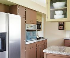 Careful Planning Kitchen appliances stayed in their original locations, greatly reducing the cost of the kitchen remodel. Most appliances were in good condition; only the microwave over the cooktop was a new purchase. Glass cabinet doors on upper cabinets at one end of the kitchen help lighten the look and show off favorite dishware.