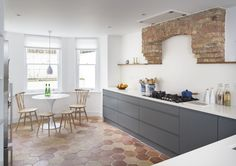 A bright and charming basement kitchen uses a clever blend of colours and tones which complement each other beautifully, creating a contemporary feel. Grey silk finished lacquered cupboard doors and draws sits beautifully on hexagonal terracotta floor tiles which bounce off the original brick work above the oven adding a traditional element to a contemporary space.