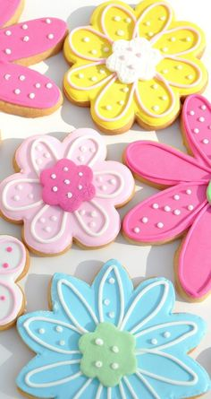 Flower decorated sugar cookies. Royal icing. Pink, yellow, blue, green. Polka dots. Five petals, eight petals, 10 petals.