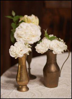 trio of vintage metal vases containing white blooms