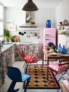 Una cocina con piezas muy vintage y muebles de obra con cortinas.