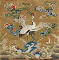 A rare embroidered civil official's 'Crane' rank badge, badge, buzi, Qing Dynasty, 18th century, made for a first rank official, embroidered in satin stitch in tones of blue, pink, green, red and white, the centre with a crane standing with one leg raised and the other supported on rockwork, its raised head turned towards the sun, amidst ruyi-form clouds, against a ground of couched gold thread, above rolling waves incorporating auspicious emblems of coral and be-ribboned musical chime.