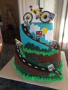 BICYCLE CAKE! Chocolate banana top layers chocolate bottom. Full Buttercream w/ Fondant accents. Triple layers in both tiers for height. Road cake tutorial -mycakeblog.com I let all the imperfections guide me for deco. Final product -A little inspiration from every bicycle cake on Pinterest! In pic bicycle is broken. It WAS solid with spaghettini and fondant, until it met my son. led to an AMAZING cheat- gluing  bike to fondant cloud, propping it up. Wish I would have thought of it in…
