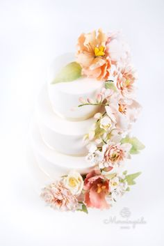Wedding cake with cascade of flowers including dahlia, peony, roses, buds and leaves.