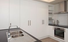 A black stone benchtop sits in this compact kitchen in Hobsonville Point, Auckland. Sink, Kitchen Cabinets, Stone Benchtop, House, Kitchen, Home, Cabinet, Home Decor, Compact Kitchen
