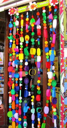 Bead Curtain made from plastic bottles. Fun for a kids room Plastic Milk Bottles, Plastic Bottle Caps, Bottle Cap Crafts, Diy Craft Projects, Fun Crafts, Kids Garden Toys, Bottle Top Art, Sensory Garden, Beaded Curtains