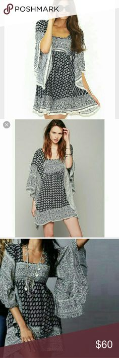 Free People Heart of Gold Bell Sleeve Dress Cute black, white and blue dress with bell sleeves, adjustable tie at waist, criss cross straps in back, Edges are frayed to give it that distressed boho look. This dress is incredibly comfortable.   Cute with black gladiators and a black floppy hat. Free People Dresses Mini