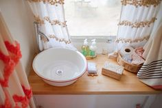 """A tiny bathroom calls for tiny accessories, so Sarah decorated accordingly. """"I cut the bath rug down so that it would fit,"""" she explains. """"The sink is made out of a old farmhouse bowl."""""""