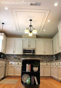 She Removed A Large Fluorescent Kitchen Box Light and used chair rail molding on the ceiling to mask where the patch was