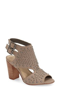 Mixed-scale dome studs pepper the smooth leather of this cutout sandal styled with a doubled slingback strap and lifted by a chunky stacked-woodgrain heel.