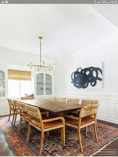 dining room with leather and woven chairs, large wood table, cozy rug, gold light fixture