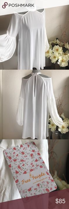 """FREE PEOPLE Blouse NWT— In the pictures the top appears to be white against the contrast color of the magnolias, but in fact the true color is """"ivory"""".  This is a flowy tunic/mini dress that indeed would be a wonderful addition to your closet for this spring and summer! Please read more information down below! 🌸☀️   -Cold open shoulders -Halter neck with button closure  -Long sleeves with elasticized cuffs -Back keyhole -Approx. 33.5"""" length  -100% Rayon  -Fits true to size Free People Tops"""
