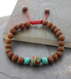 Natural Tibetan raktu beads with a beautiful hand inlaid vintage Tibetan spacer and two turquoise spacer beads. Adjustable wrist mala measures approximately 6 i