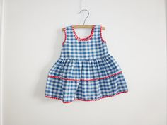 Good condition dress. No tags attached. Handmade. It is blue and white gingham with red polka dot trim on the edges. There is some