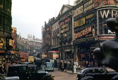 """Piccadilly Circus in All the people are wearing brown, grey, black. Cars mainly come in any colour you like so long as it's black. A giant cigarette in an ashtray advertises Craven """"A"""" high above Piccadilly Circus. London Pictures, London Photos, Photos Du, Old Photos, Artsy Photos, Stock Photos, Piccadilly Circus, Vintage London, Old London"""