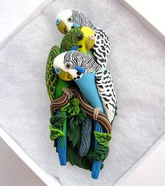 Custom birdy pin featuring three parakeets hand sculpted without molds or paint from polymer clay. On FlickR, the artist's first name is alicia and her handle is parrotjewelry.