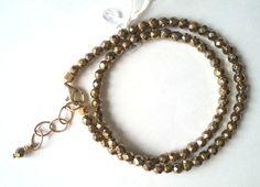 Dubbele armband in goud-gekleurde ronde hematiet met karabijn slot en verlengkettinkje. Lengte = 17-21 cm