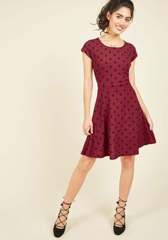 While teaching the time-tested steps of your favorite dance in this burgundy dress, you give a bonus lesson in fabulous, feminine style! Offering textured fabric and black dots to your lively tutorial, this American-made A-line holds your students' attention, and inspires them all the same.