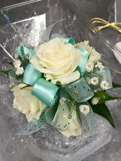 Wristlet corsage with White spray roses, baby's breath, powder blue sparkle ribbon, mint green ribbon, clear rhinestones and silver sparkle accents. #prom #corsage #wristlet #flowers #theflowershopfairoaks