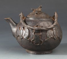 An unusual carved iron teapot featuring bats. Japan, early 20th century, width: 5.0 in. height: 4.1 in.