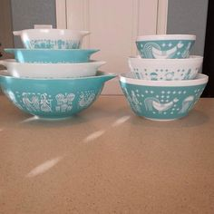 """Vintage Pyrex Butterprint nesting bowls on the left sitting next to """"Vintage Charm"""" Rise & Shine mixing bowls on the right."""