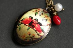 A handmade locket necklace designed with an 18mm x 24mm bronze locket, hand-screened with picture of a trio of pretty robins together on a