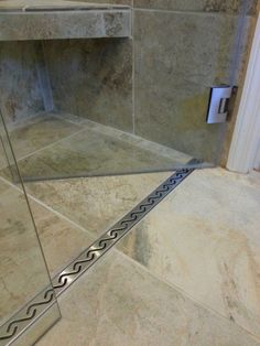 Linear drain in front of glass door in no-threshold shower