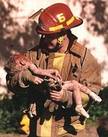 A firefighter is holding a dying toddler in his arms, and he is looking down at her. The toddler has blood on her head, arms, and legs, and is wearing white socks. (Oklahoma City bombing, April 19th 9:02am)