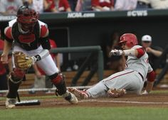 Indiana's Kyle Schwarber slides in to score Indiana's first run in the first inning against Louisville in Saturday's second College World Series game in Omaha. (By Matt Stone, The Courier-Journal) June 15, 2013