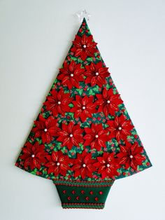 Requinte e sofisticação : uma linda árvore decorada com as flores do espírito santo !  É um painel revestido com tecido e aplicada as flores do espírito santo , artesanalmente produzidas em camadas de feltro na cor vermelho escuro . O resultado final é rico em detalhes , com brilho e elegância.  Acabamentos de chaton , pérolas e passamanaria enriquecem o conjunto , com uma linda estrela na ponta . O verso do painel é revestido em feltro liso verde…