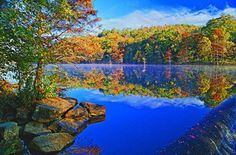 Vibrant fall foliage reflects on Broken Bow Lake at Beavers Bend State Park in southeastern Oklahoma.