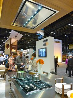 +ARTESIO Kitchen design by Poggenpohl in walnut finish - On display at the KBIS 2012 Show in Chicago. The integrated ventilation extractor with LED lighting is shown above the built-in cooktop.