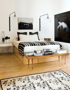 Cush and Nooks: Lofty Heights, black and white master bedroom, wall mount lights, light wood bench
