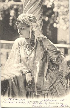 Algerian woman wearing a fringed scarf and silver jewelry.