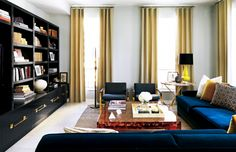 7 Bad Décor Shopping Habits to Stop Right Now// Sectional sofa with square coffee table and wall of built-in shelving