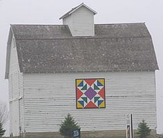 Geometric barn quilt on a pretty old white barn.