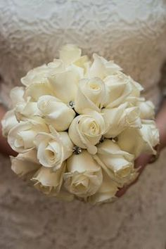 All-white roses with a little bling incorporated within the blooms is the perfect amount of sparkle and beauty for your all-white ensemble. Don't you agree?  #wedding #rosepetalevents #weddingplanner #bouquet #rose  Photo Source: https://pixabay.com/en/bouquet-wedding-bride-673155/